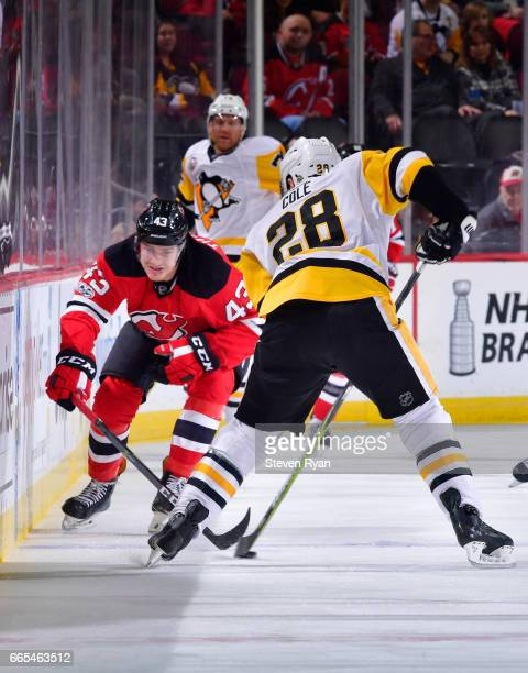 Ian Cole of the Pittsburgh Penguins plays the puck while being defended by Ben Thomson of the New Jersey Devils during an NHL game at Prudential...