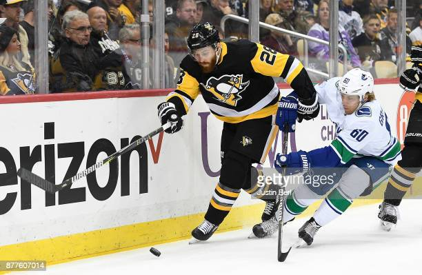 Ian Cole of the Pittsburgh Penguins skates for a loose puck against Markus Granlund of the Vancouver Canucks in the first period during the game at...