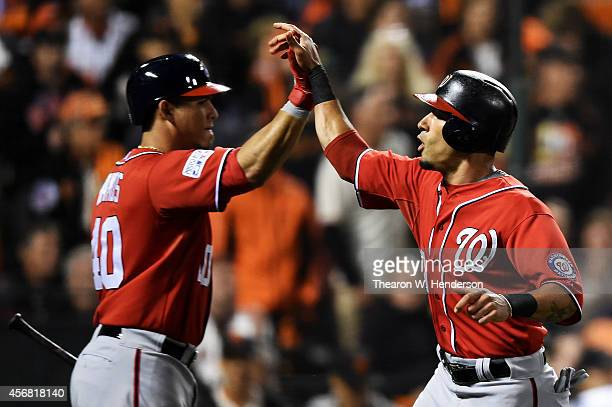 Ian Desmond celebrates with Wilson Ramos of the Washington Nationals after scoring on a RBI double by Bryce Harper in the fifth inning against the...