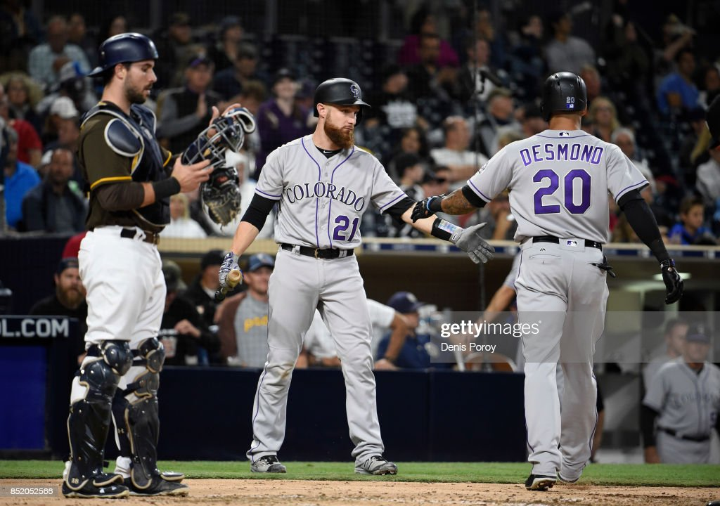 Ian Desmond #20 of the Colorado Rockies is congratulated by Jonathan Lucroy #21 after hitting a solo home run during the fifth inning of a baseball game against the San Diego Padres at PETCO Park on September 22, 2017 in San Diego, California.