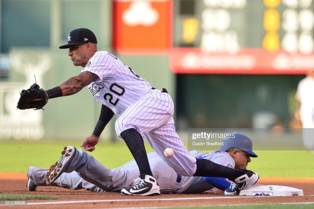Ian Desmond #20 of the Colorado Rockies misses a low throw on a double play attempt as Manny Machado #8 of the Los Angeles Dodgers dives back to first base in the first inning of a game at Coors Field on August 9, 2018 in Denver, Colorado. Mach ado advanced to second base on the play.