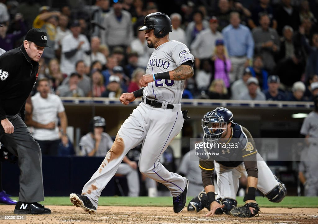Ian Desmond #20 of the Colorado Rockies scores ahead of the throw to Austin Hedges #18 of the San Diego Padres during the seventh inning of a baseball game at PETCO Park on September 22, 2017 in San Diego, California.