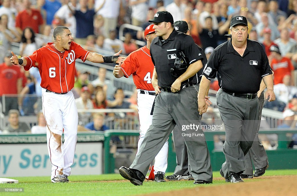 Ian Desmond #6 of the Washington Nationals argues with home plate umpire Dan Bellino and first base umpire Joe West after being called out at third base in the seventh inning against the Cincinnati Reds at Nationals Park on June 4, 2010 in Washington, DC.