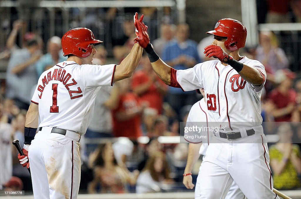 Ian Desmond #20 of the Washington Nationals celebrates with teammate Steve Lombardozzi #1 after hitting a home run in the seventh inning against the Colorado Rockies at Nationals Park on June 21, 2013 in Washington, DC. Washington won the game 2-1.