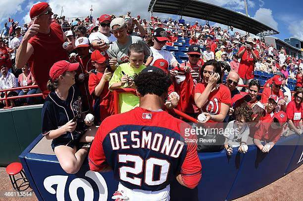 Ian Desmond of the Washington Nationals signs autographs for fans prior to a spring training game against the Houston Astros at Space Coast Stadium...