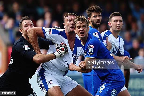 Ian Evatt of Chesterfield holds off the challenge of Ryan Clarke the AFC Wimbledon goalkeeper and Paul Robinson of AFC Wimbledon during the Sky Bet...