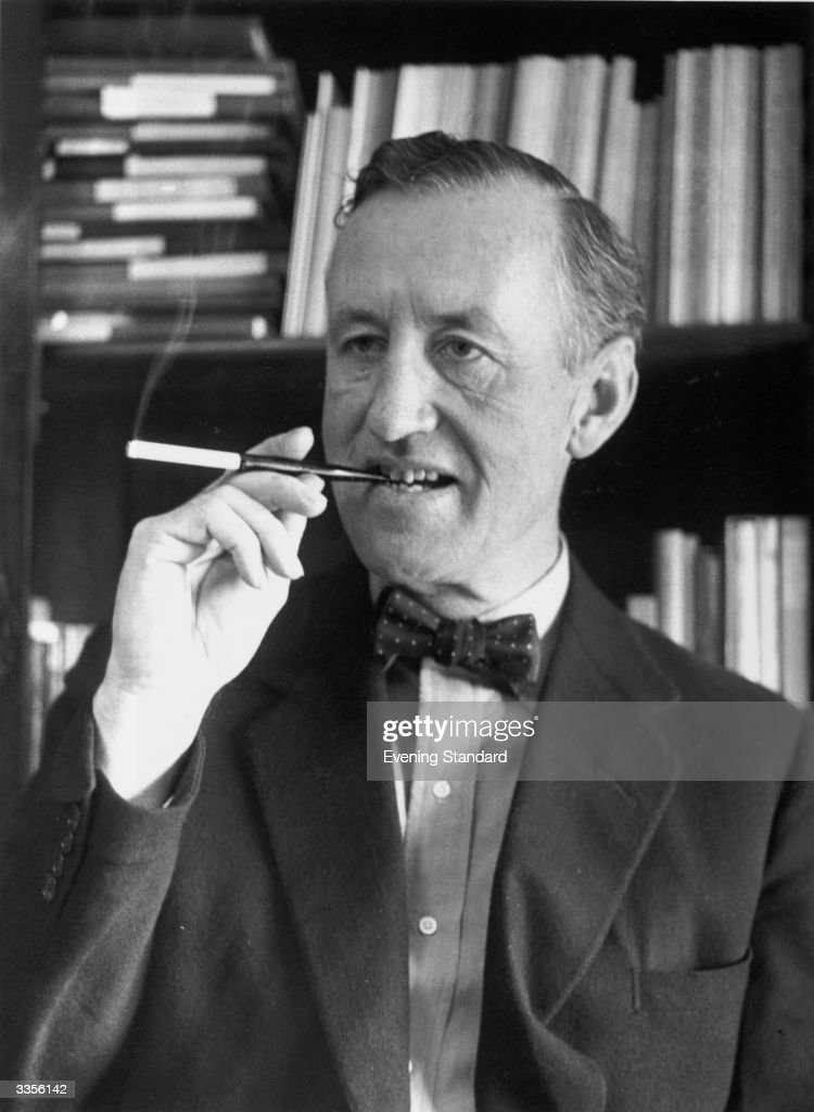 Ian Fleming, British author and creator of James Bond, smoking with a cigarette holder.