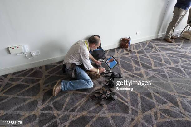 Ian Forsyth, a freelance photographer, edits images of Jeremy Hunt, U.K. Foreign secretary, on a laptop computer, during his speech at the U.K....