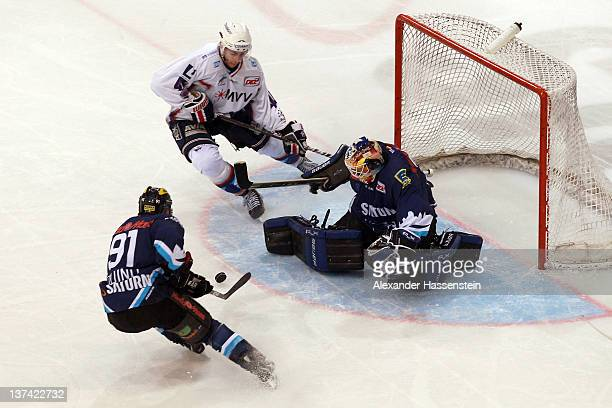 Ian Gordon, goalie of Ingolstadt and his team mate Luciano Aquino challenge for the puck with Matthias Plachta of Mannheim during the DEL match...