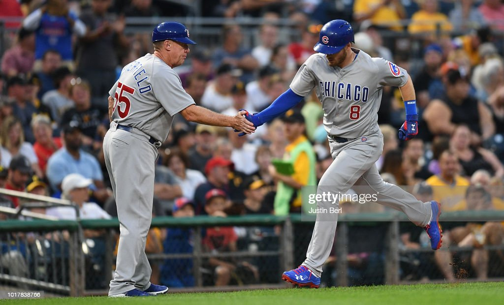 Ian Happ #8 is greeted by Brian Butterfield #55 of the Chicago Cubs as he rounds the bases after hitting a solo home run in the fourth inning during the game against the Pittsburgh Pirates at PNC Park on August 16, 2018 in Pittsburgh, Pennsylvania.