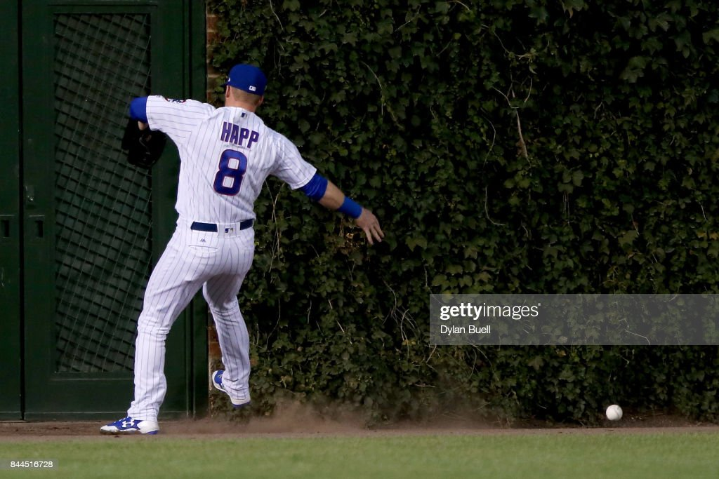 Ian Happ #8 of the Chicago Cubs chases after a fly ball hit by Eric Thames #7 of the Milwaukee Brewers in the first inning at Wrigley Field on September 8, 2017 in Chicago, Illinois.
