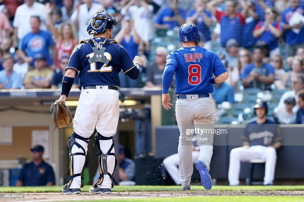 Ian Happ #8 of the Chicago Cubs crosses home plate to score a run past Stephen Vogt #12 of the Milwaukee Brewers in the tenth inning at Miller Park on September 23, 2017 in Milwaukee, Wisconsin.