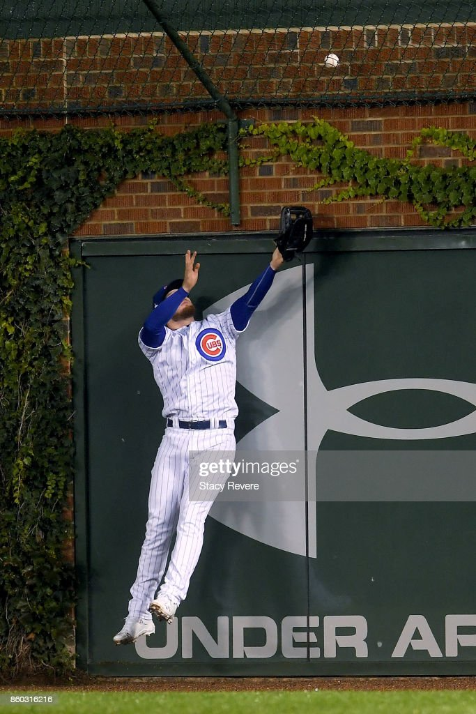 Ian Happ #8 of the Chicago Cubs fails to catch a grand slam hit by Michael Taylor #3 of the Washington Nationals in the eighth inning during game four of the National League Division Series at Wrigley Field on October 11, 2017 in Chicago, Illinois.