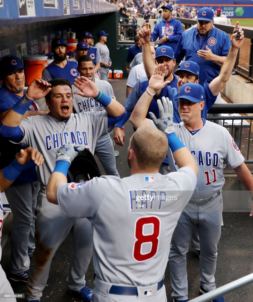 Ian Happ #8 of the Chicago Cubs is congratulated by Kyle Schwarber #12 and the rest of his teammates in the dugout after he hit a grand slam in the second inning against the New York Mets on June 13, 2017 at Citi Field in the Flushing neighborhood of the Queens borough of New York City.