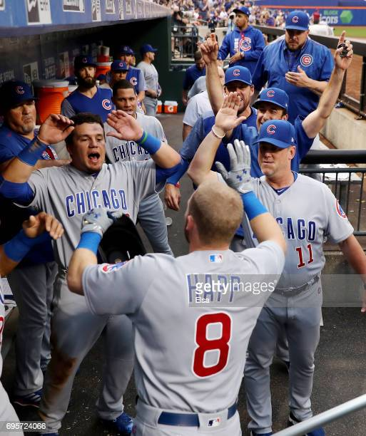 Ian Happ of the Chicago Cubs is congratulated by Kyle Schwarber and the rest of his teammates in the dugout after he hit a grand slam in the second...