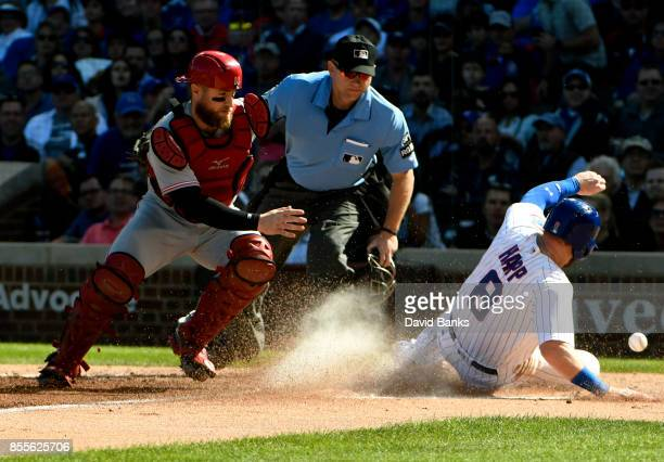 Ian Happ of the Chicago Cubs is safe at home plate as Tucker Barnhart of the Cincinnati Reds can't handle the throw during the second inning on...