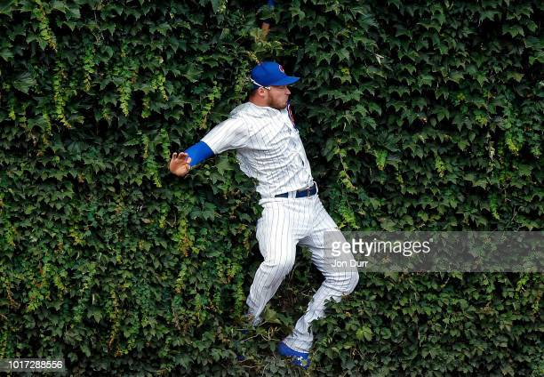 Ian Happ of the Chicago Cubs makes a leaping catch for an out against the Milwaukee Brewers and collides with the outfield wall during the ninth...