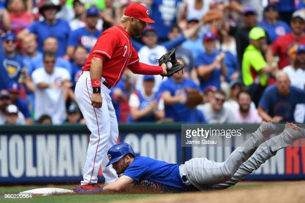 Ian Happ of the Chicago Cubs slides in for a triple as Eugenio Suarez of the Cincinnati Reds takes the throw in the sixth inning at Great American...