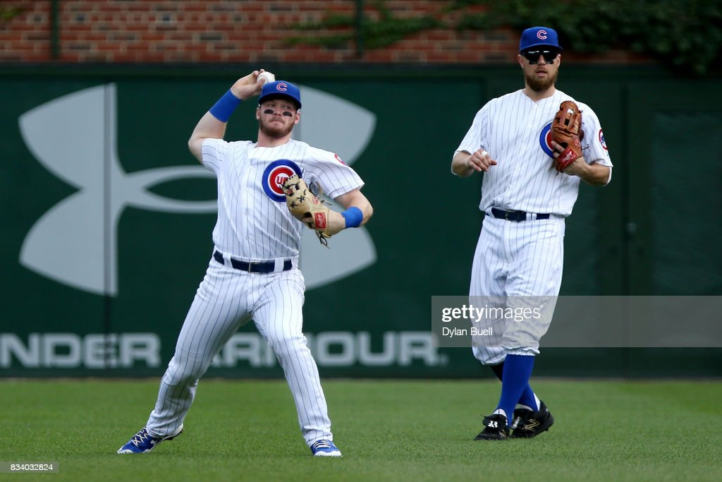 Ian Happ #8 of the Chicago Cubs throws the ball to the infield as teammate Ben Zobrist #18 looks on in the second inning against the Cincinnati Reds at Wrigley Field on August 17, 2017 in Chicago, Illinois.