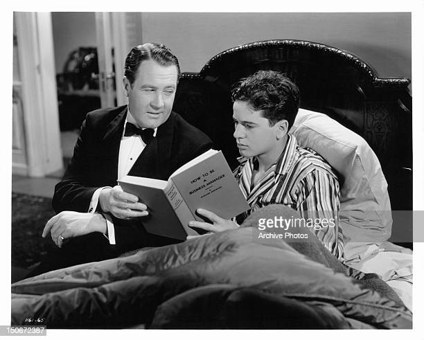 Ian Hunter sharing book with Gene Reynolds in a scene from the film 'Gallant Sons' 1940