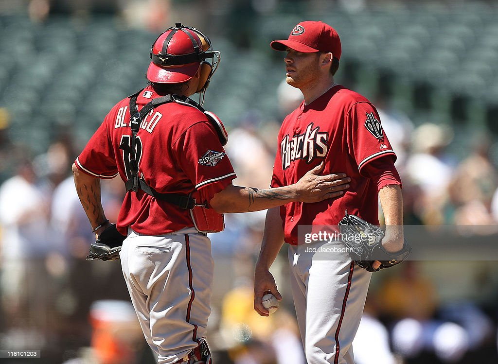Ian Kennedy #31 of the Arizona Diamondbacks speaks with catcher Henry Blanco #12 of the Arizona Diamondbacks after giving up a home run to Scott Sizemore of the Oakland Athletics at Oakland-Alameda County Coliseum on July 3, 2011 in Oakland, California.