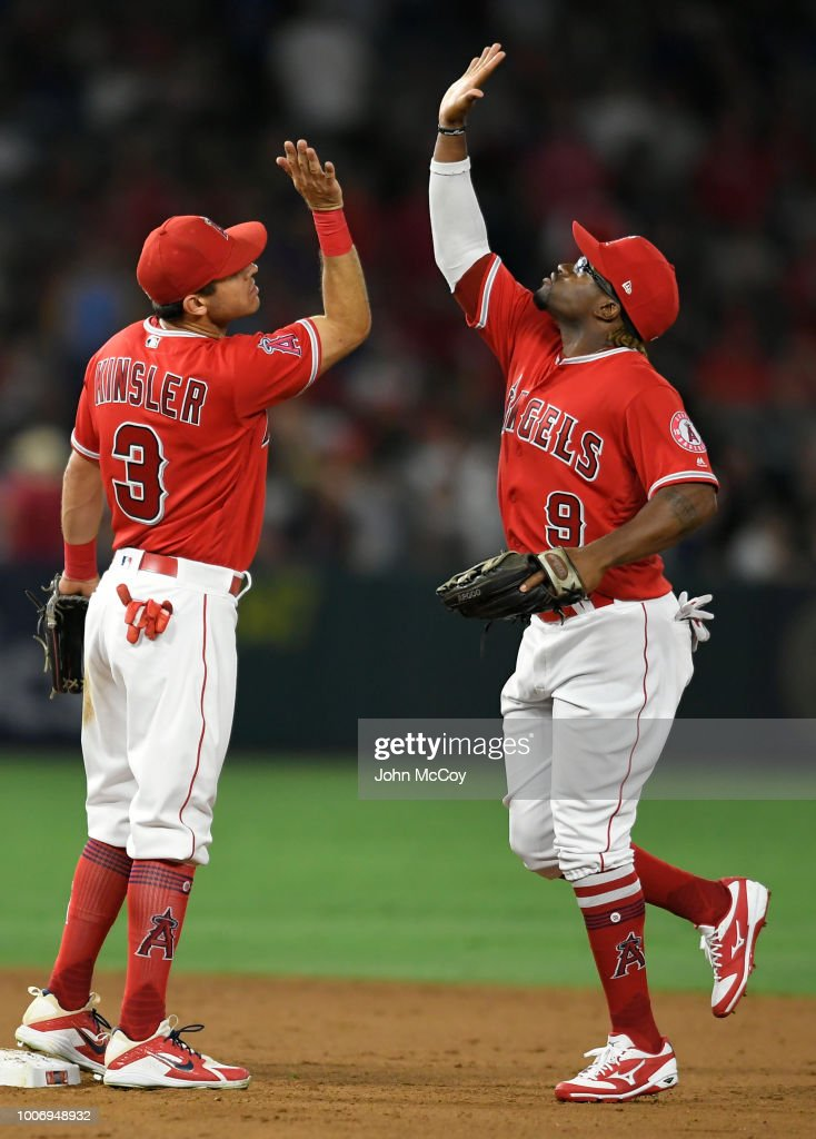Ian Kessler #3 of the Los Angeles Angels of Anaheim gives a high five to Eric Young Jr. #9 after defeating the Seattle Mariners 11-5 at Angel Stadium on July 28, 2018 in Anaheim, California.