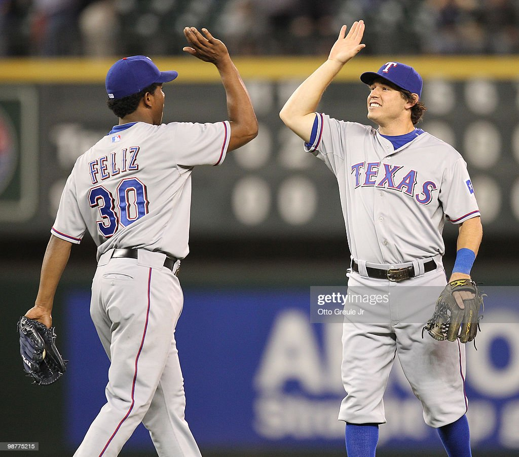 Ian Kinsler #5 and Neftali Feliz #30 of the Texas Rangers celebrate after defeating the Seattle Mariners 2-0 in twelve innings at Safeco Field on April 30, 2010 in Seattle, Washington.