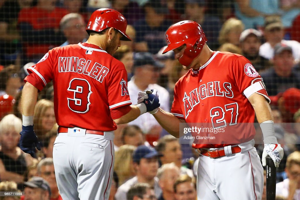 Ian Kinsler #3 high fives Mike Trout #27 of the Los Angeles Angels after hitting a solo home run in the fifth inning of a game against the Boston Red Sox at Fenway Park on June 27, 2018 in Boston, Massachusetts.