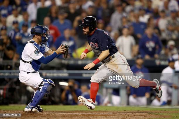 Ian Kinsler of the Boston Red Sox is tagged out at home plate by Austin Barnes of the Los Angeles Dodgers on a throw from Cody Bellinger during the...