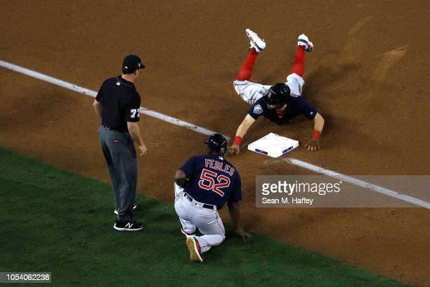 Ian Kinsler of the Boston Red Sox slides in safely against the Los Angeles Dodgers during the tenth inning in Game Three of the 2018 World Series at...