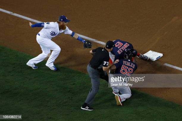 Ian Kinsler of the Boston Red Sox slides in safely to third base as Justin Turner of the Los Angeles Dodgers fields the ball during the tenth inning...
