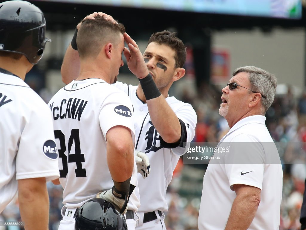 Ian Kinsler #3 of the Detroit Tigers and trainer Kevin Rand check out James McCann #34 after he was hit in the head by a pitch in the seventh inning while playing the New York Yankees at Comerica Park on August 24, 2017 in Detroit, Michigan.