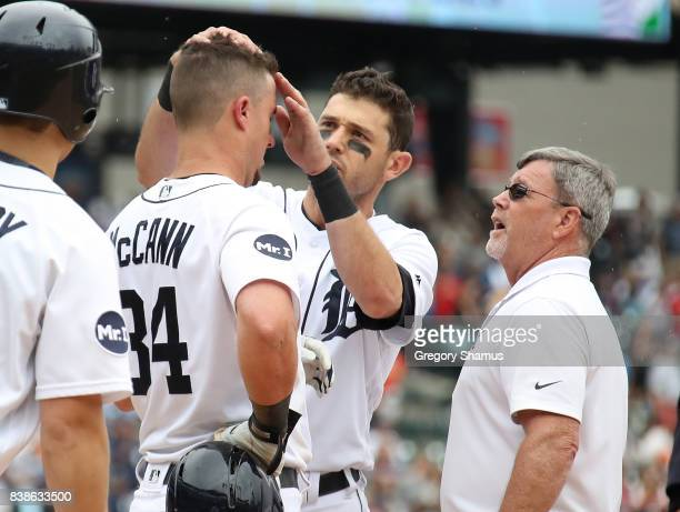 Ian Kinsler of the Detroit Tigers and trainer Kevin Rand check out James McCann after he was hit in the head by a pitch in the seventh inning while...