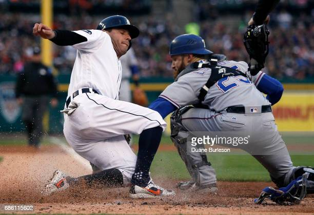 Ian Kinsler of the Detroit Tigers beats the tag from catcher Jonathan Lucroy of the Texas Rangers to score from third base on a ground out by Miguel...