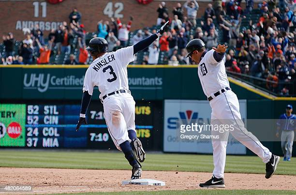Ian Kinsler of the Detroit Tigers celebrates his 10th inning game winning RBI single with first base coach Omar Vizquel to beat the Kansas City...