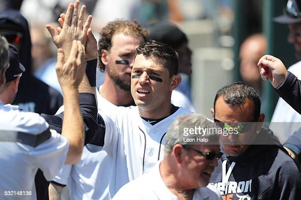 Ian Kinsler of the Detroit Tigers celebrates with his teammates in the dugout after scoring on the JD Martinez single during the first inning of the...