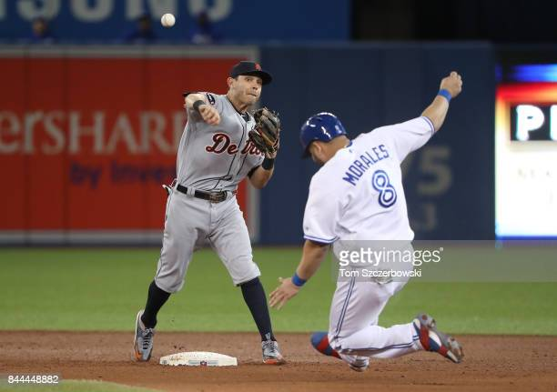 Ian Kinsler of the Detroit Tigers turns a triple play in the sixth inning during MLB game action as Kendrys Morales of the Toronto Blue Jays slides...