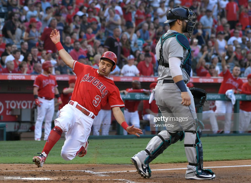 Ian Kinsler #3 of the Los Angeles Angels of Anaheim crosses home plate behind Mike Zunino #3 of the Seattle Mariners in the second inning at Angel Stadium on July 28, 2018 in Anaheim, California.