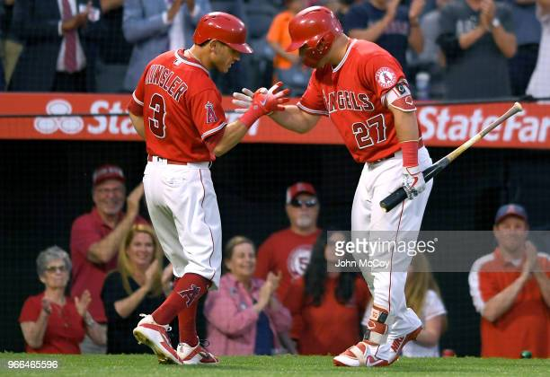Ian Kinsler of the Los Angeles Angels of Anaheim is congratulated by Mike Trout for the sixth inning home run against the Texas Rangers at Angel...