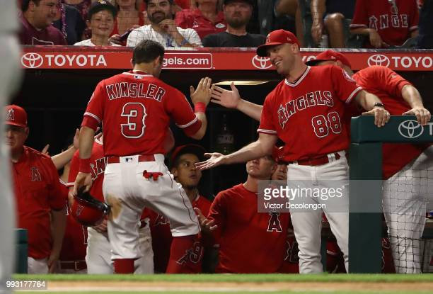 Ian Kinsler of the Los Angeles Angels of Anaheim is congratulated by teammates as he enters the dugout after scoring in the sixth inning during the...