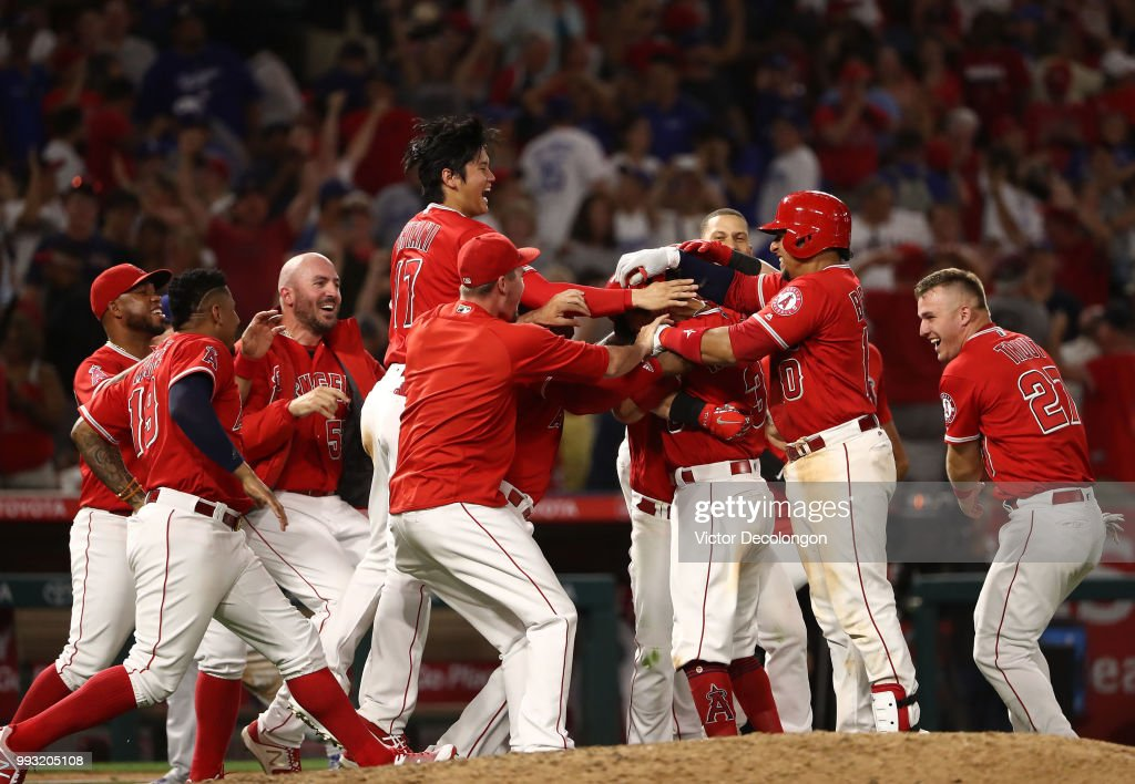 Ian Kinsler #3 of the Los Angeles Angels of Anaheim is mobbed by teammates after hitting a single to right field which resulted in the winning run scoring on a throwing error by Yasiel Puig #66 of the Los Angeles Dodgers (not in photo) to home plate in the ninth during the MLB at Angel Stadium on July 6, 2018 in Anaheim, California. The Angels defeated the Dodgers 3-2.