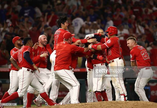 Ian Kinsler of the Los Angeles Angels of Anaheim is mobbed by teammates after hitting a single to right field which resulted in the winning run...