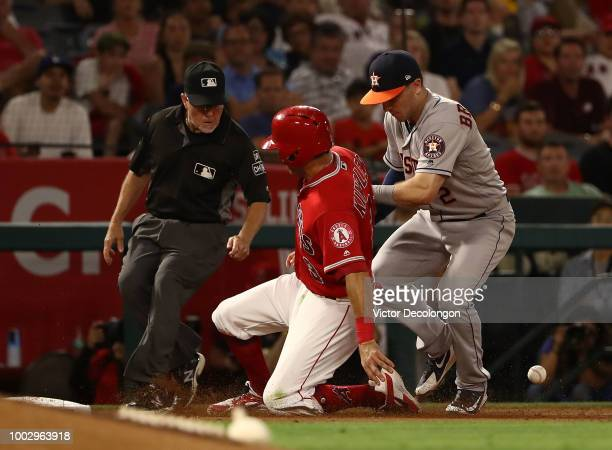 Ian Kinsler of the Los Angeles Angels of Anaheim slides safely into third base after Alex Bregman of the Houston Astros failed to catch the ball as...