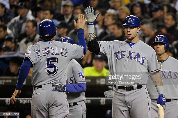 Ian Kinsler of the Texas Rangers celebrates after scoring on a single by Elvis Andrus with Josh Hamilton in the sixth inning of Game Four of the...