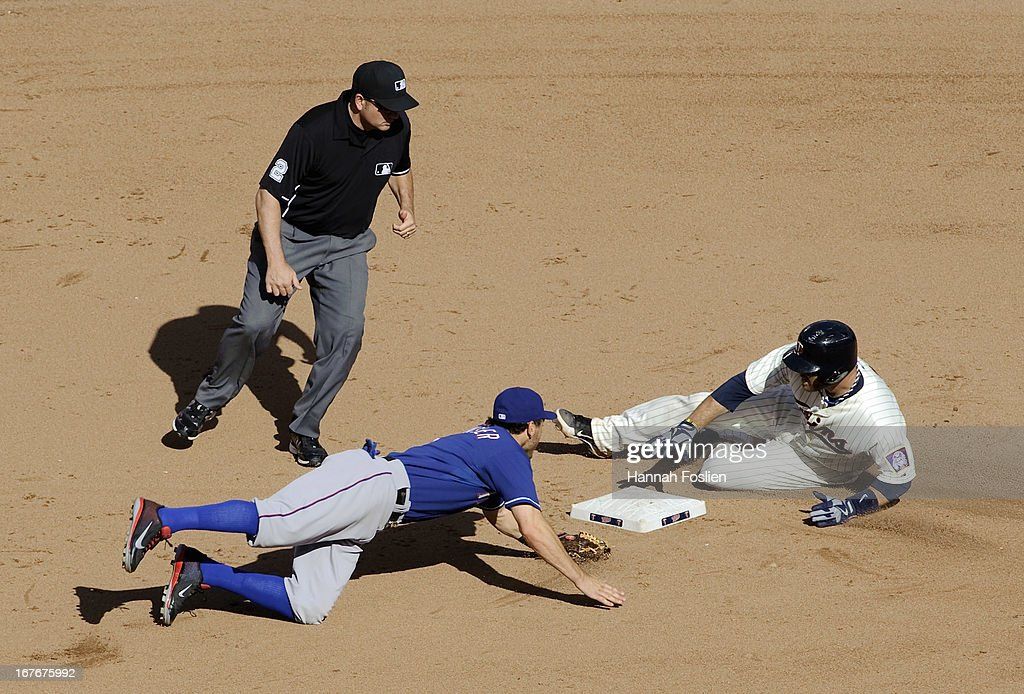 Ian Kinsler #5 of the Texas Rangers dives to second base as Ryan Doumit #9 of the Minnesota Twins slides safely with a double as umpire Dan Bellino #2 looks on during the sixth inning of the game on April 27, 2013 at Target Field in Minneapolis, Minnesota. The Twins defeated the Rangers 7-2.