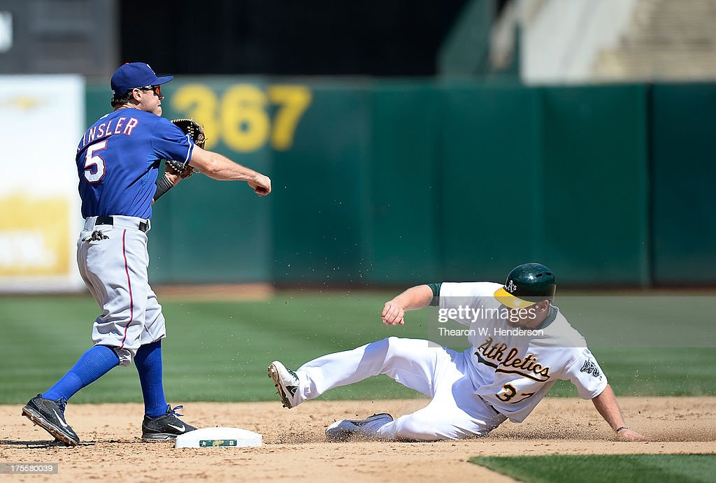 Ian Kinsler #5 of the Texas Rangers gets his throw off to complete the double-play as Brandon Moss #37 of the Oakland Athletics slides into second base in the ninth inning at O.co Coliseum on August 4, 2013 in Oakland, California. The double-play ended the game with the Rangers winning 4-0.