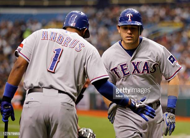 Ian Kinsler of the Texas Rangers gives teammate Elvis Andrus a five after Kinsler leads off with a home run in the first inning off Jeremy Hellickson...