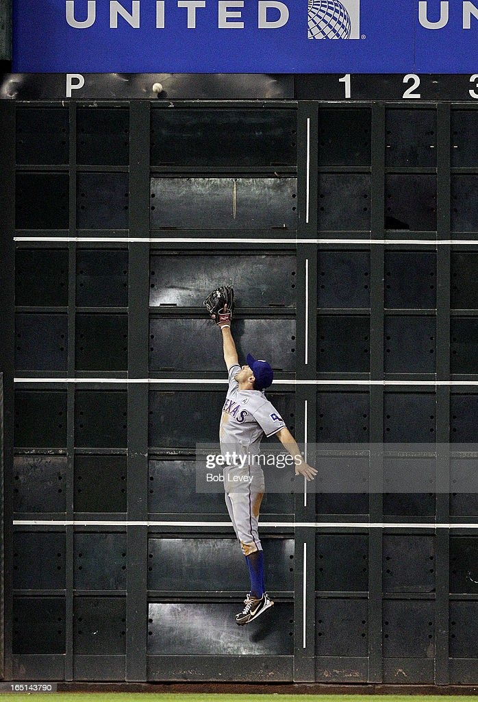 Ian Kinsler #5 of the Texas Rangers leaps at the wall but can't make a catch on a ball hit by Justin Maxwell #44 of the Houston Astros on Opening Day at Minute Maid Park on March 31, 2013 in Houston, Texas.