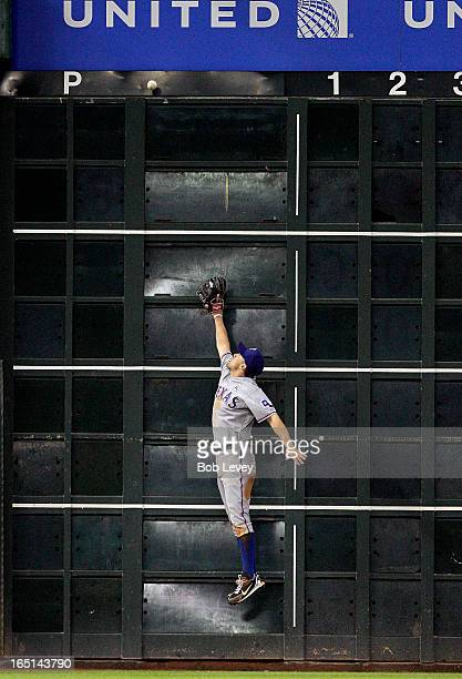 Ian Kinsler of the Texas Rangers leaps at the wall but can't make a catch on a ball hit by Justin Maxwell of the Houston Astros on Opening Day at...