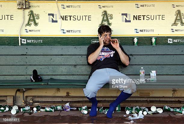 Ian Kinsler of the Texas Rangers smokes a cigar and speaks on his cell phone in the dugout after the Rangers beat the Oakland Athletics to clinch the...